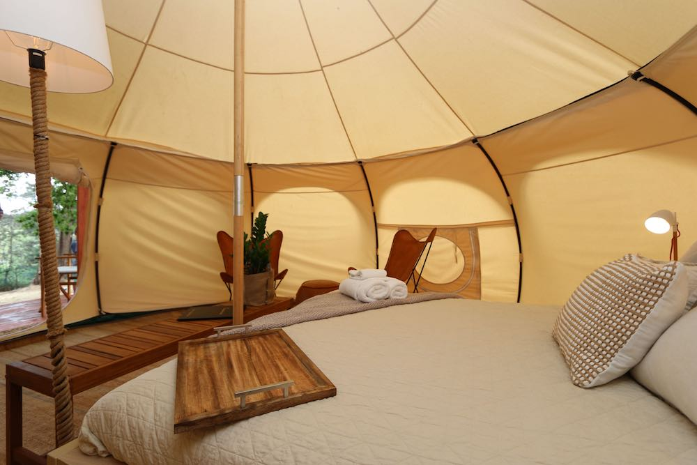 Glamping shot of bed and seating area in large tent